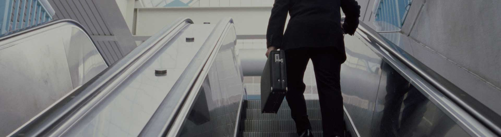 business man going up on escalator