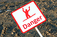 Danger sign with outlined image of man sinking into quicksand.