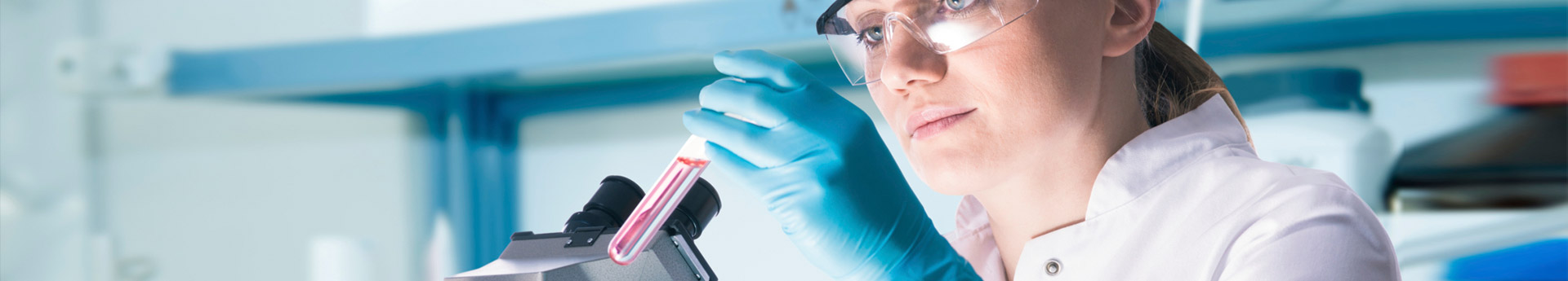 Woman in clinical or scientific laboratory examining a test tube