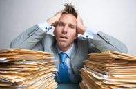 Frustrated man with tons of paperwork